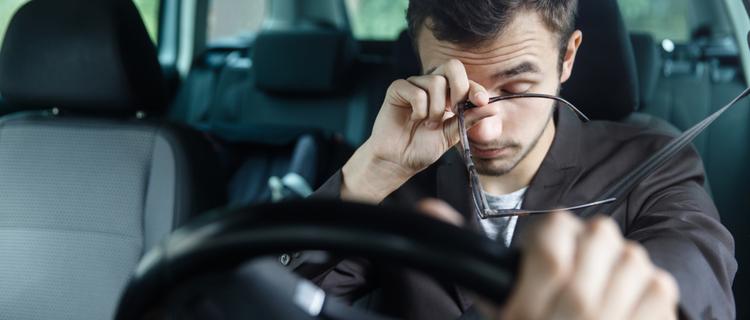目をこする運転中の男性