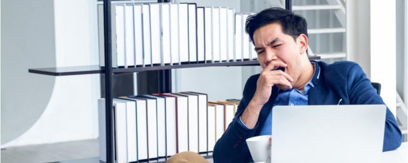 パソコンの前で欠伸をする男性会社員