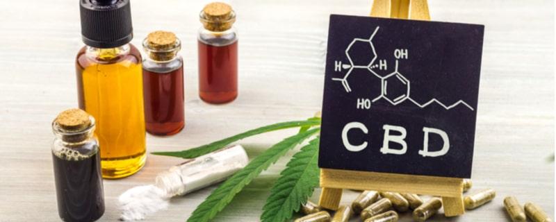 大麻の葉とCBD構造式の書かれた黒板とオイルの瓶