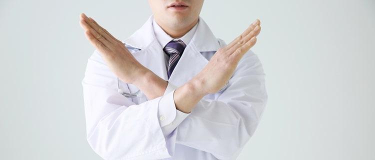 両手でバツを作る医師