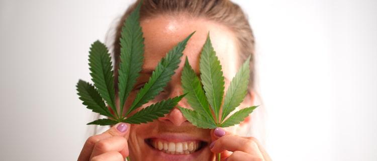 大麻の葉で目を隠す笑顔の女性