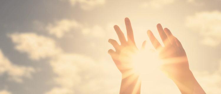 手の間からもれる太陽の光